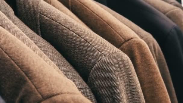 Řádek teplé Pánské bundy na závěs na Pánské oděvy obchod v obchoďáku. Různé Pánské obleky visí v nákupním centru