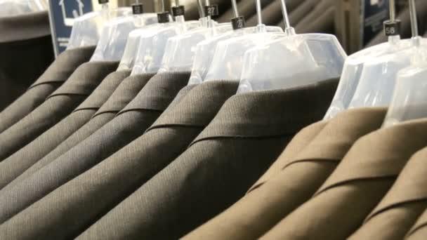 Hnědé a šedé Pánské bundy Pověste na ramínkách v obchodě s oděvy Pánské v obchoďáku. Obrovskou škálu Pánské obleky na ramínkách v nákupním centru detailní zobrazení
