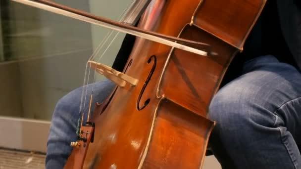 Straßenmusiker, der Cello aus nächster Nähe spielt. Cellist in Handschuhen spannt sanft Saiten