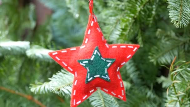 Christmas tree toy in the shape of star of red color from wool fabric decorated with glass beads that hangs on a branch