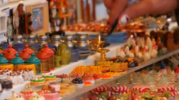 Female hand chooses decorative Christmas and New Year trifles on the counter of Christmas market