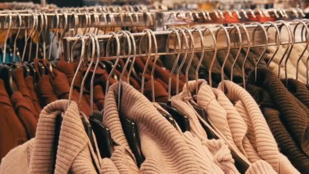 Velký počet Dámské teplé oblečení visí na ramínkách a leží na policích v obchodě s oděvy obchodní centrum nebo mall. Problém konzumu