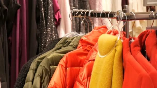 Různé pestrobarevným teplé dámské oblečení na ramínkách v obchodě s oděvy v obchoďáku nebo nákupní centrum