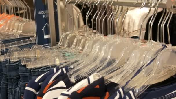 Různé pestrobarevným Dámské oděvy a džíny visí na ramínkách v obchodě s oděvy v obchoďáku nebo nákupní centrum