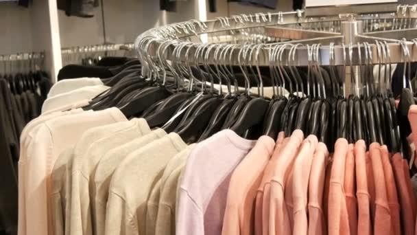 Na velké kulaté ramínko existují různé stylové barevné svetry visí na módní černé závěsy v obchodě s oděvy v obchoďáku nebo nákupní centrum detailní zobrazení