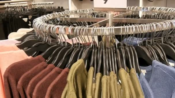 On a big round hanger there are various stylish knitted multicolored sweaters hanging on fashion black hangers in a clothing store in a mall or shopping center, close up view