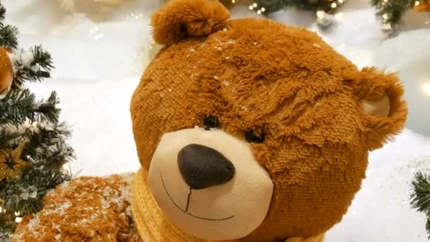 Toy brown bear as a decor near beautifully dressed Christmas tree in a mall or shopping center
