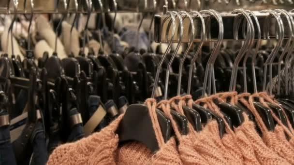 Velký počet nových teplé stylové svetry různých barev, visí na ramínkách v oblečení ukládat nákupní centrum nebo mall. Módní kolekce teplé oblečení.