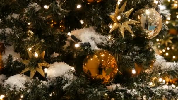 Beautifully decorated Christmas tree with large gold and silver balls, stars, garlands and artificial snow is standing in the shopping center close up view