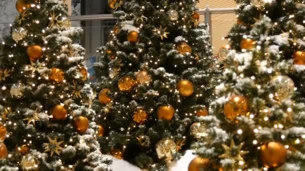 Tři krásně vyzdobený vánoční strom s velkými zlaté a stříbrné koule, hvězdy, girlandy a umělý sníh stojí v nákupním centru