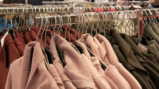 Large number of new warm stylish sweaters of different colors hanging on hangers in the clothing store shopping center or mall, Fashionable collection of warm clothes.
