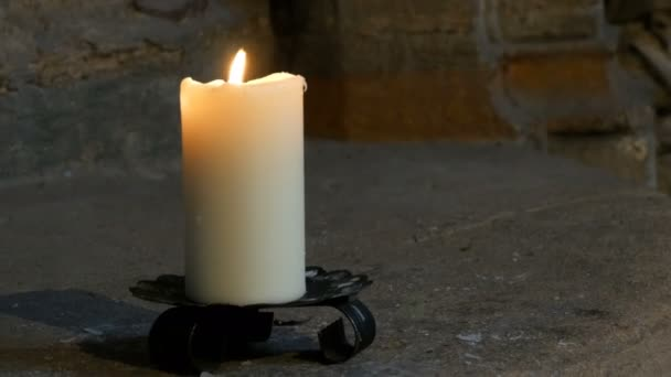 Large wax white candle burns and stands in an old candlestick in an old medieval church in Germany.