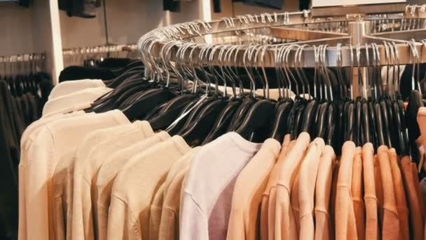 b05fdae31 Fashionable youth clothes hanging on hangers in a clothing store in a  shopping center.– stock footage