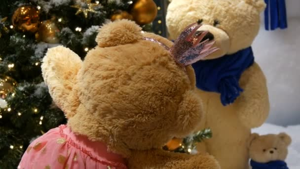 Princess toy brown teddy bear in a dress and crown spinning around in a Christmas-decorated shopping center