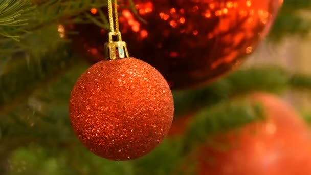 Beautiful stylish Christmas tree toy balls of red color hangs on the Christmas tree close up view. New Years and Christmas decor.