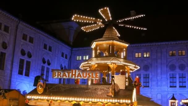 München - 2. Dezember 2018: Christkindlmarkt in der Kaiserlichen Residenz. antike Weihnachtsmühle im Lichterglanz, in der Holzfiguren Weihnachten darstellen.