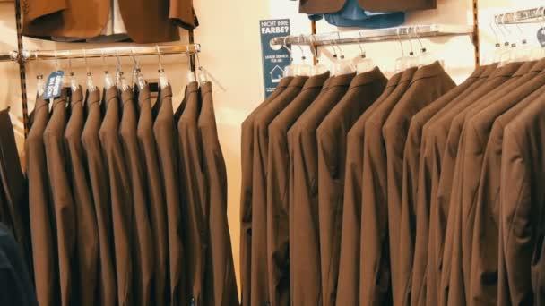 Počet stejných barevné Pánské obleky, zavěšení na ramínko v obchodě s oděvy v obchoďáku