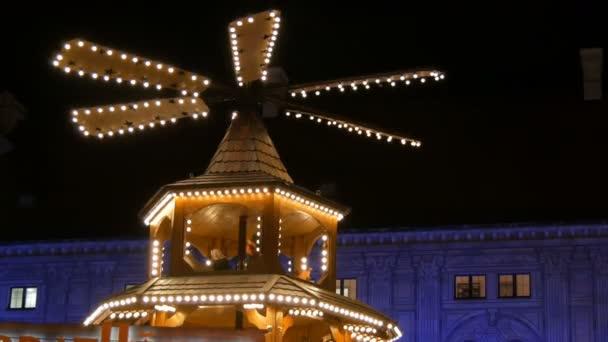 Christkindlmarkt in der kaiserlichen Residenz in München. Teil der antiken Weihnachtsmühle in den Lichtern, in der Holzfiguren Weihnachten darstellen.