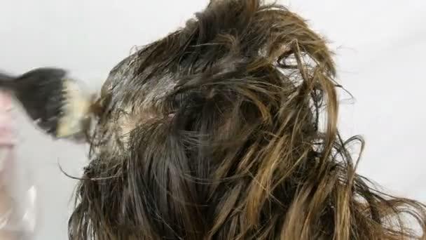 Šedé vlasy na kořenech žen, které samy barví vlasy se speciální barvou a štětcem doma