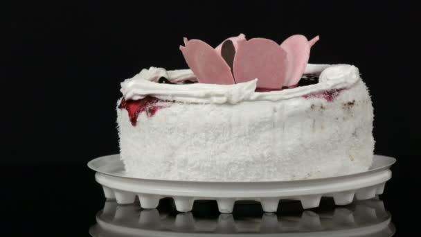 Gyönyörű stílusos édes friss fehér sütemény cseresznye lekvárral díszített tetején tejszín és kókusz chips forog a fekete háttér.