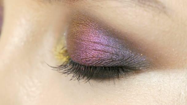 Módní vícebarevné oční stíny chameleon s žlutá fialová šedá stříbrná na víčko modelu krásná dívka s hnědýma očima. Profesionální kosmetické make-up. Pohled zblízka pohled