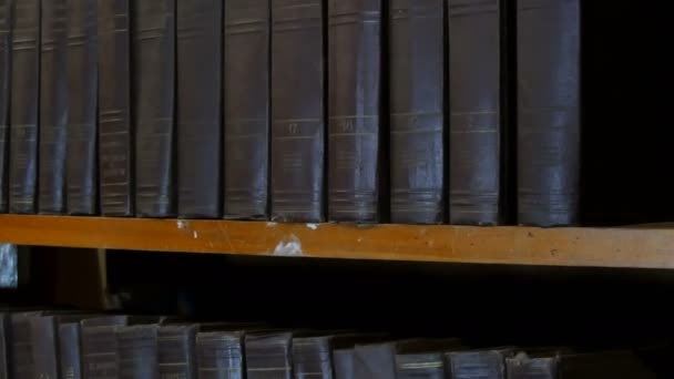 Row of big old black books on a bookshelf in library.