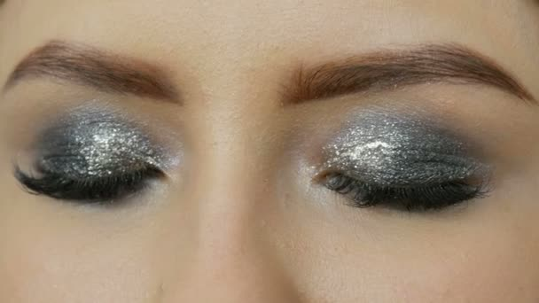 Makeup artist makes models smoky eyes with the help of special gray eyeshadow, eyes and eyelashes of girl close up view. Professional high fashion.