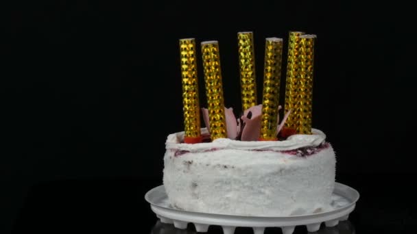Gyertyák egy gyönyörű stílusos, édes, friss fehér sütemény cseresznye Jam díszített tejszín és kókusz pehely a tetején. Születésnapi torta fekete alapon.