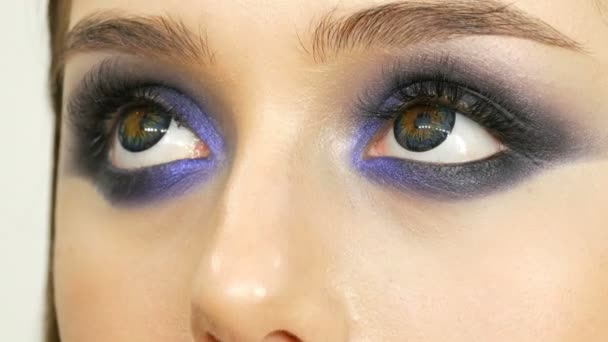 Young beautiful sexy girl models make blue evening make up smoky eyes and with false eyelashes. Eyes with multi-colored contact lenses
