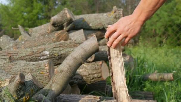 Muž dřevořezník sekal dřevo starou ocelovou sekyrou. Ručně řezané dřevo