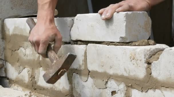 Mužský tvůrce, který položil bílou cihlu na cement a stojnou zeď. Ruce člověka pokládané za stavební cihly zblízka