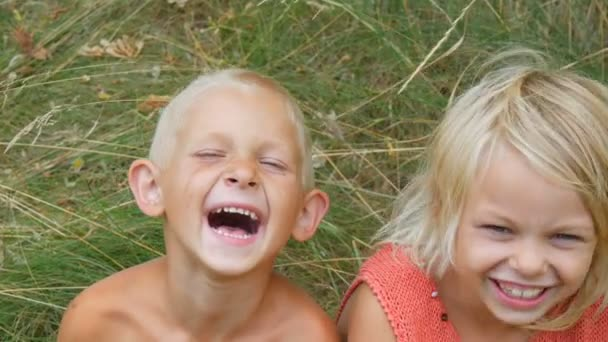 Funny dirty faces children blonde brother and sister make faces laugh smile and have fun in village on nature on a summer day