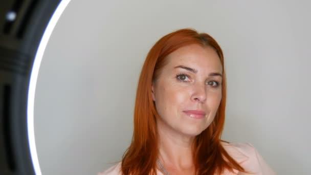 Krásná zrzavá dospělá ženská modelka ve středním věku, která pózala před kamerou ve studiu