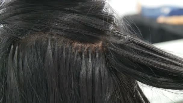 Hosszú, szép, fekete haj hajcsavaró stylist fürtök. Hajformázó és curling. Hajhosszabbító kapszula a fejen