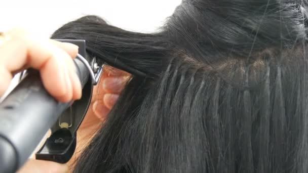 Dlouhé, nádherné černé vlasy kulma kadeřavé. Vlasová úprava a curling. Nástavce na prodlužování vlasů na hlavě