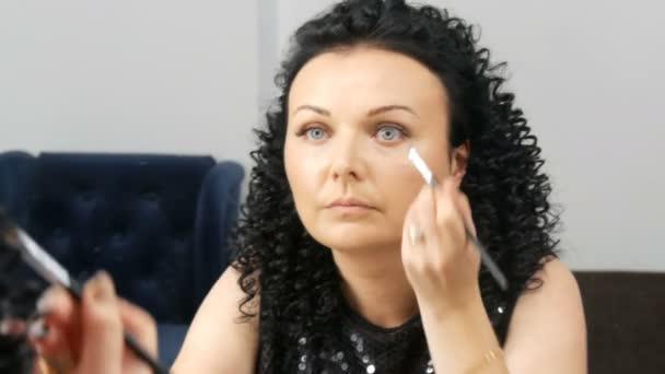 Krásná mladá brunetka se kudrnatými černými vlasy se líčí před zrcadlem.