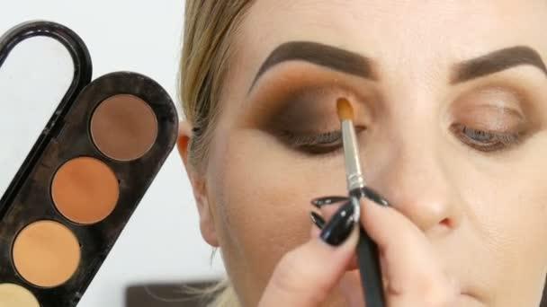 Profesionální umělec na make-up aplikuje paletu béžová stínový stín se speciálním kartáčem na modelový oko u kosmetický salon v těsném pohledu