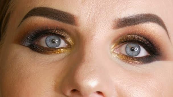 Krásná tlustá ženská modelka se zlatým líčením, zakouřené oči tmavě červené rtěnky falešné řasy a modré oči pózové na černém pozadí ve studiu. Pohled zblízka na obličej
