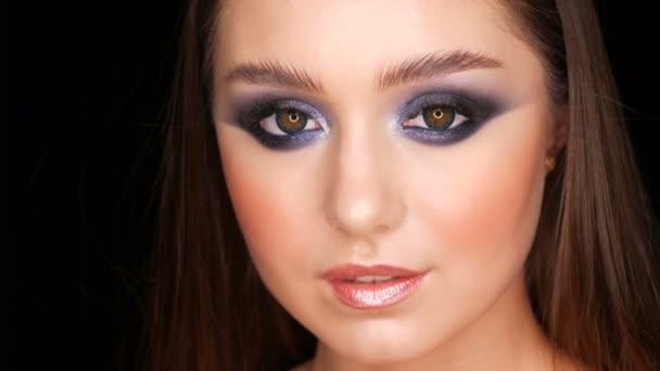 sexy zarte schöne junge Model mit langen Haaren und blauem Abend Make-up rauchige Augen posieren vor der Kamera auf schwarzem Hintergrund. Model mit langen Wimpern und breiten Augenbrauen flirtet