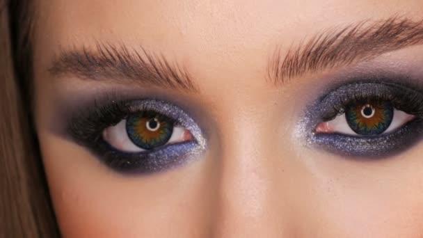 Krásná mladá dívka s večerním modrým make-up a kosmetickými barevnými kontaktními čočkami pohled zblízka