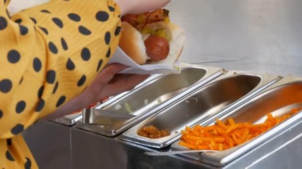 Dívky v rukou si na Hot Dogu vydělají různá ochutka ve speciálním stánku pouličních jídel, rychlé občerstvení na ulici Amsterdam.