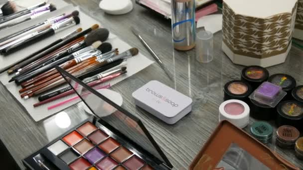 Kamjanskoe, Ukrajina-16. březen 2019: profesionální kosmetika na stole v ateliéru. Vícebarevné rtěnky, stíny, základ v make-up módním průmyslu