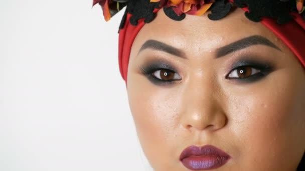 Gyönyörű koreai ázsiai lány egy trendi vörös turbán fényes esti make-up füstös szeme pózol stúdióban fehér alapon