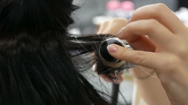Detailní pohled na ženské kadeřnice stylista dělá kadeř kudrlin vlasů se speciálním curling železo. Dlouhé krásné vlasy černé a bílé barvy mladé ženy barvené pomocí ombre techniky