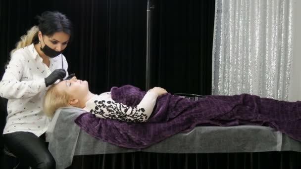 Krásná mistryně v modelování tvaru obočí provádí korekci obočí ke svému klientovi, který leží na gauči v salónu krásy. Mikrobladění, tetování, permanentní make-up