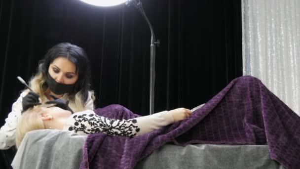 Gyönyörű nő stylist sminkes művész kozmetológus teszi szemöldök korrekció a beteg arcát, amely fekszik egy speciális kanapén elegáns szépség stúdió fekete-ezüst függönyök