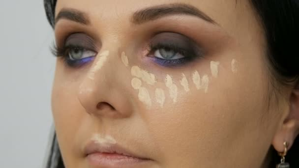 Face contouring makeup artist leads a woman in the face with a brush for applying powder, foundation or concealer. Lilac and pearly smoky eyes eyeshadow, eyes and face of a woman close up