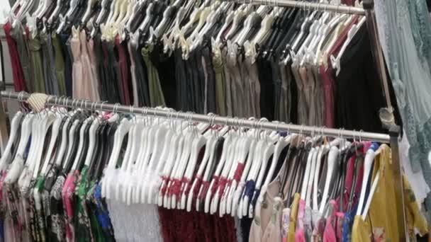 Různé dámské oblečení visí v řadě na ramínka v obchodě s oblečením