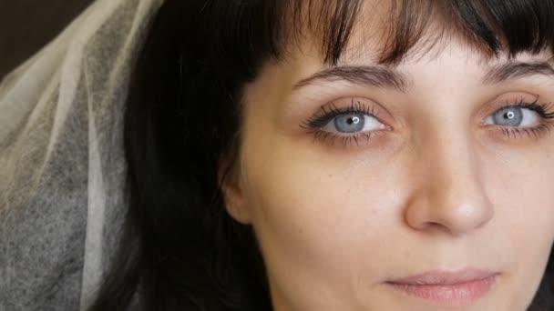 The face portrait of a beautiful young woman with blue eyes and long eyelashes before the procedure of permanent make up by microblading with eyebrow tattoo lies on a couch in a beauty salon