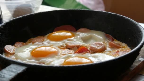 Chutná čerstvě smažená vejce ve staré litinové pánvi, s kořením, rajčaty, sladkou paprikou a klobásami, s párou. Ranní snídaně, kulaté vaječné žloutky v kuchyni